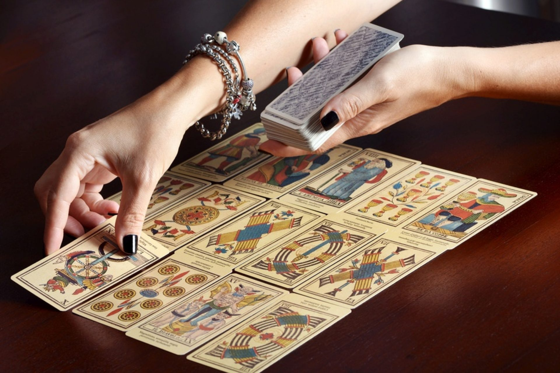 Female fortune tellers hands spreading vintage tarot cards on dark table surface